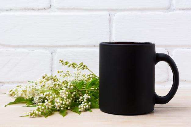 Maquette de tasse à café noire avec des fleurs de spiraea blanches