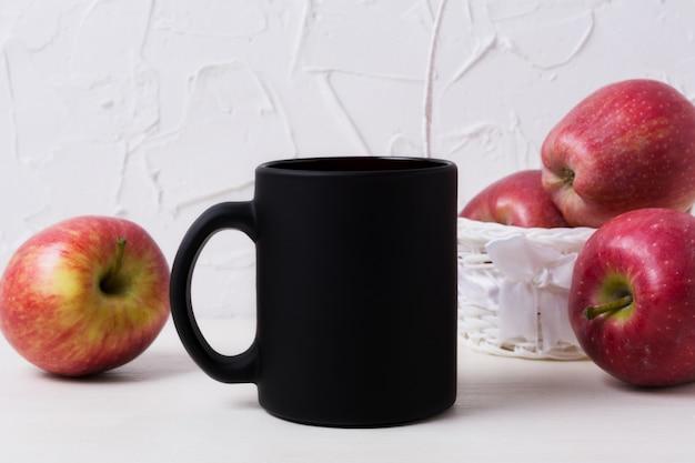 Maquette de tasse à café noire avec des pommes dans un panier blanc