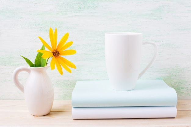 Maquette de tasse de cappuccino blanc avec des fleurs de rosarin jaune dans un pichet