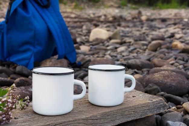 Maquette de tasse de deux feux de camp blancs avec sac à dos bleu