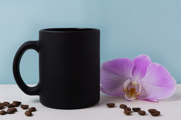 Maquette de tasse noire avec orchidée et grains de café