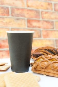 Maquette de tasse en papier avec des pâtisseries au café de la ville, mur de briques sur fond
