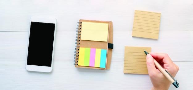 Maquette de téléphone et bannière de note papier vierge, main tenant un stylo sur le bloc-notes vierge et téléphone intelligent avec modèle d'écran vierge