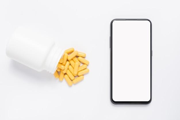 Maquette de téléphone et bouteille de médicament avec des pilules jaunes.