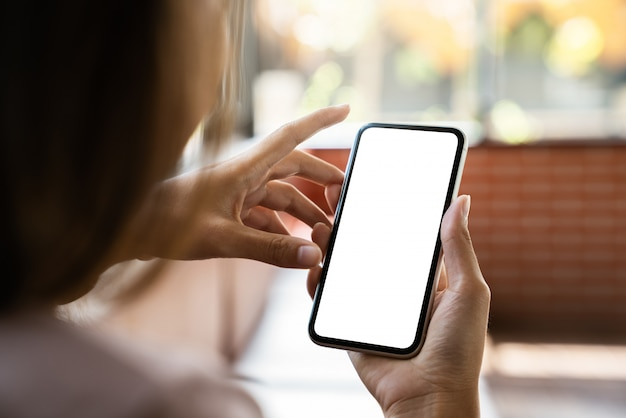 Maquette de téléphone dans la main de la femme montrant un écran blanc