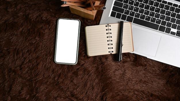 Maquette de téléphone intelligent avec écran blanc et ordinateur portable sur un tapis en fourrure marron.