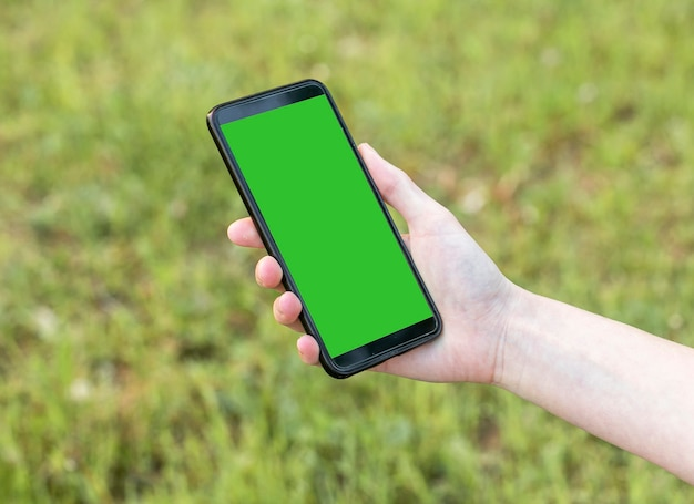 Maquette de téléphone mobile moderne avec un modèle d'écran vide dans une main féminine sur l'herbe verte