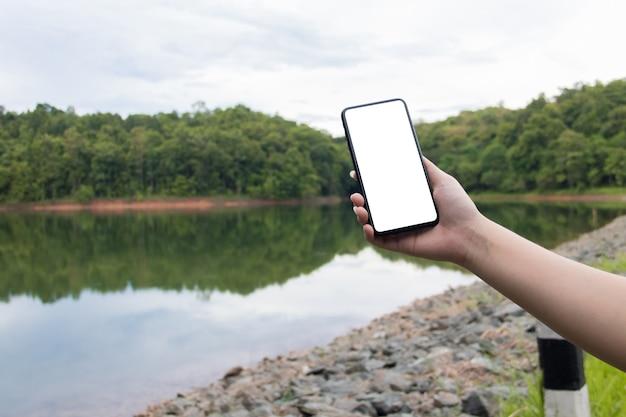 Maquette de téléphone portable sur le bord de la rivière avec fond de nature verdoyante. concept d'entreprise