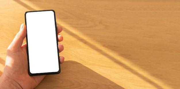 Maquette de téléphone portable avec écran blanc pour votre application annonce dans la main masculine sur fond en bois, gros plan. lumière du jour.