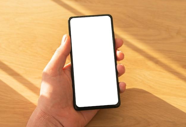 Maquette de téléphone portable avec écran blanc pour votre application ou site en main masculine sur fond en bois, gros plan. lumière du jour.