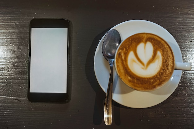 Maquette de téléphone portable par une tasse de café