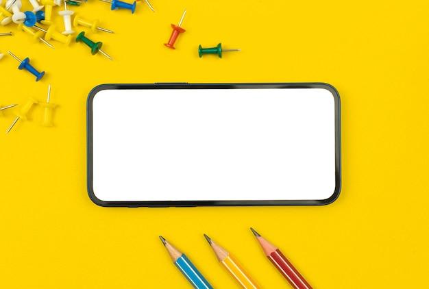 Maquette de téléphone portable pour l'éducation, table de bureau jaune avec fournitures et équipement scolaires, épingles et crayons de couleur, vue de dessus avec photo de l'espace de copie