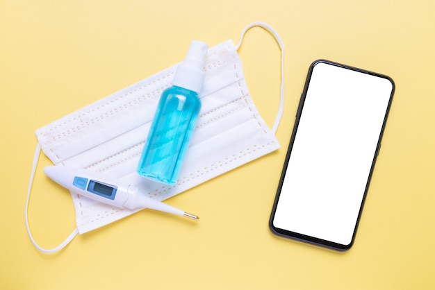 Maquette de téléphone avec spray d'alcool, thermomètre numérique et masque facial sur fond jaune.