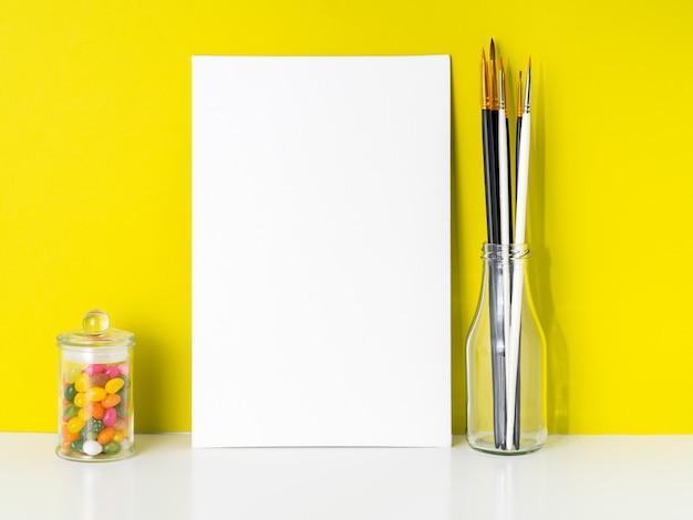 Maquette en toile blanche, bonbons dans un bocal, pinceaux sur fond jaune vif. concept