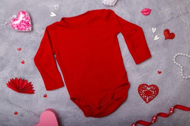 Maquette de vêtements de bébé rouges à plat avec un décor pour la saint-valentin pour vos logos et textes