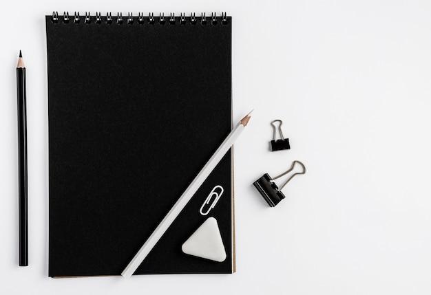 Maquette vierge de cahier noir, crayons et papeterie sur fond blanc.
