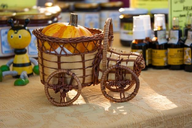 Maquette d'une voiture en bois et osier utilisée comme décoration dans un stand de marché.