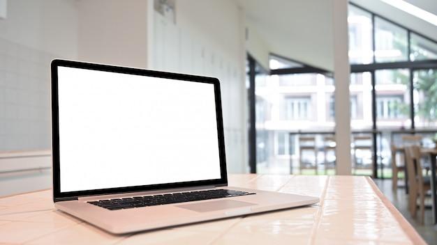 Maquette vue de côté ordinateur portable sur un comptoir dans la salle de cuisine.