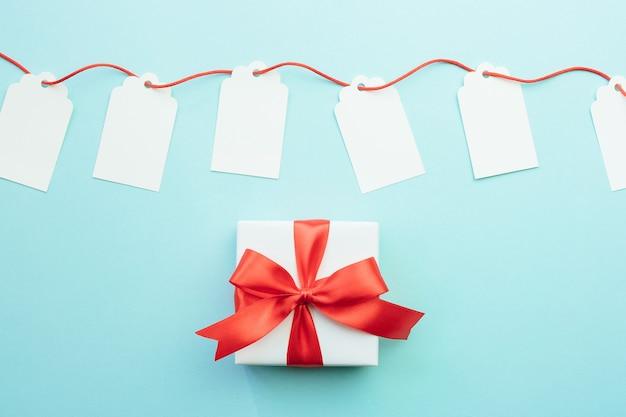 Maquettes d'étiquettes cadeaux vierges avec ruban rouge et boîte-cadeau avec noeud sur fond bleu. concept de remise ou de vente.
