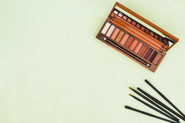 Maquillage des arbustes et palette en bois fard à paupières avec miroir sur fond vert menthe