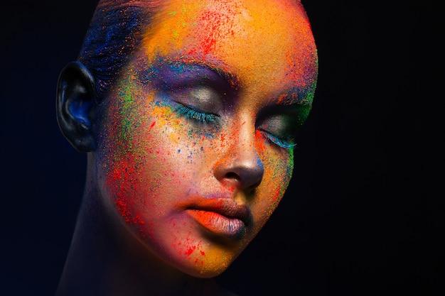 Maquillage d'art créatif. portrait de jeune mannequin aux yeux fermés et mélange de couleurs vives de peinture sur son visage. fantaisie de couleur, maquillage artistique.