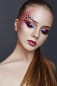 Maquillage artistique sur les sourcils avec de nombreux strass de formes différentes