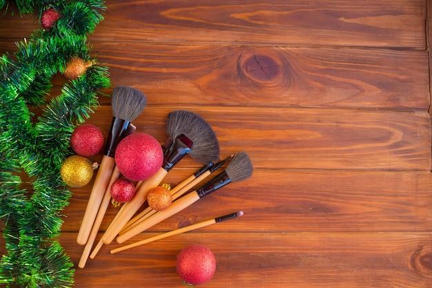 Maquillage au moment de noël. pinceau de maquillage sur fond de bois. donner du maquillage comme cadeau de noël