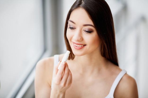 Maquillage. belle jeune femme appliquant du rouge à lèvres
