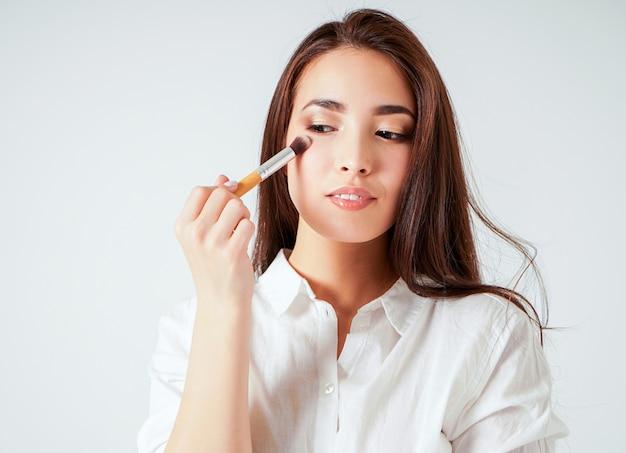 Maquillage brosse dans la main de la souriante jeune femme asiatique avec de longs cheveux noirs sur blanc