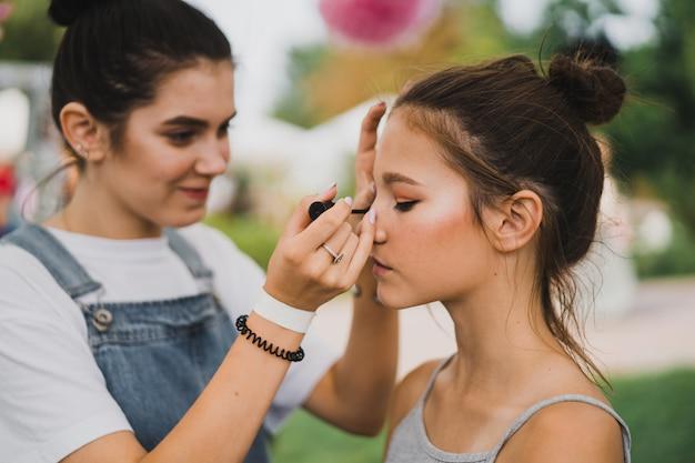 Maquillage classe de maître. fille se maquille à son amie