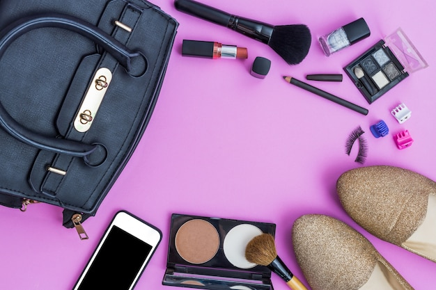 Maquillage avec des cosmétiques décoratifs et smartphone sur fond rose