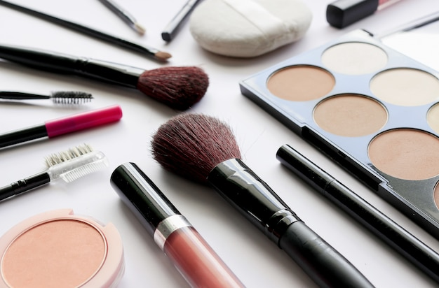 Maquillage cosmétiques sur une table blanche avec plus de lumière et flou en arrière-plan