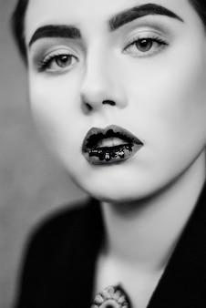 Maquillage créatif de lèvres liquides noirs en gros plan photo noir et blanc.