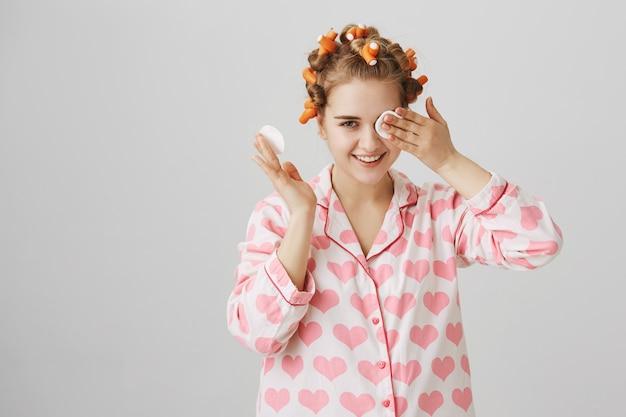 Maquillage de décollage fille mignonne avant de dormir avec un coton, portant des bigoudis et un pyjama