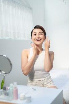 Maquillage du visage de la belle jeune femme asiatique sur fond blanc