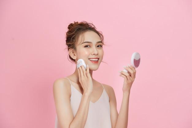 Maquillage du visage. gros plan d'une belle femme asiatique appliquant un fond de teint en poudre sèche à la recherche dans le miroir.