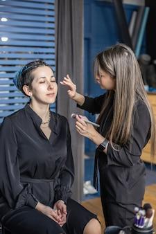 Maquillage de femme maître appliquant le teint de la peau poudre de fond de teint blush sur le visage utiliser le pinceau au salon de beauté