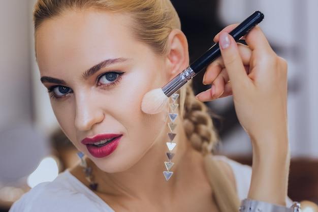 Maquillage de finition. belle femme aux lèvres rouges portant de belles boucles d'oreilles finissant son maquillage