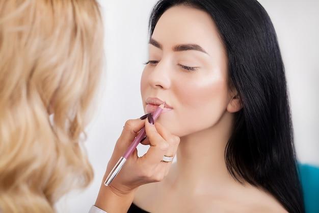 Maquillage. maquilleuse professionnelle appliquant du rouge à lèvres
