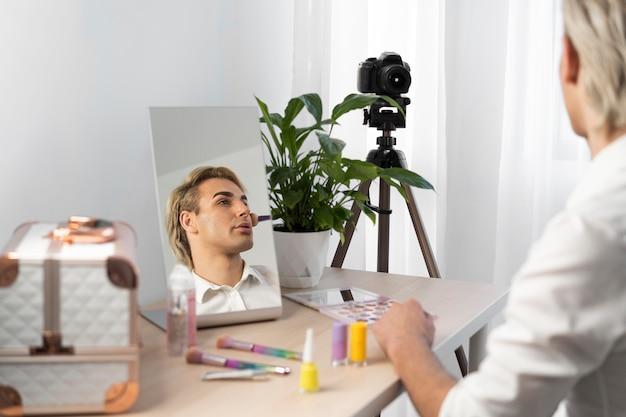 Maquillage masculin à l'aide d'un pinceau à maquillage