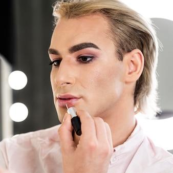 Maquillage masculin à l'aide de rouge à lèvres