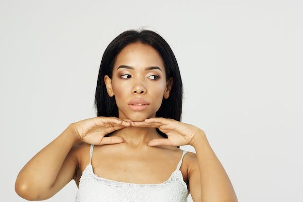 Maquillage de mode d'apparence africaine de femme posant le gros plan du visage