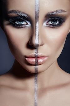 Maquillage parfait, bande de couleur argentée sur le visage de la fille, sourcils argentés et cheveux brune noire. maquillage créatif sur le visage de la femme, beaux grands yeux.