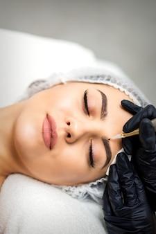 Maquillage permanent sur les sourcils de la jeune femme par un outil de tatouage spécial