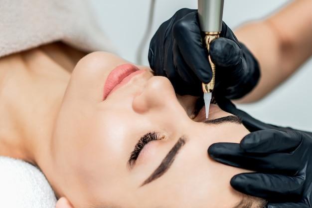 Maquillage permanent des sourcils par une cosmétologue professionnelle.