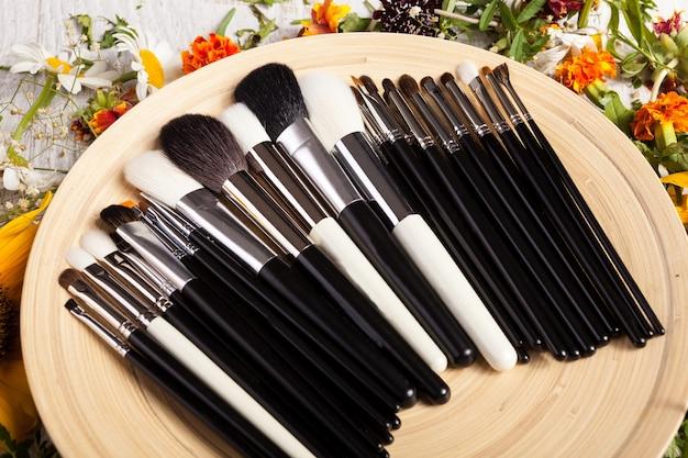 Maquillage des pinceaux sur une assiette à côté de fleurs sauvages sur fond de bois