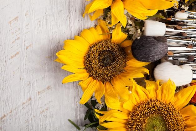 Maquillage des pinceaux à côté de belles fleurs sauvages sur fond de bois