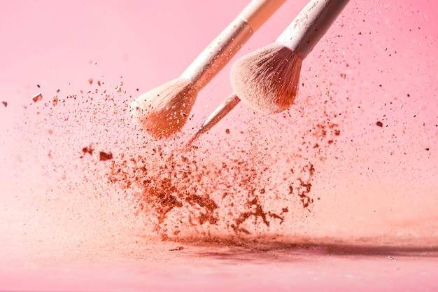 Maquillage pinceaux avec éclaboussures de poudre isolé sur fond rose