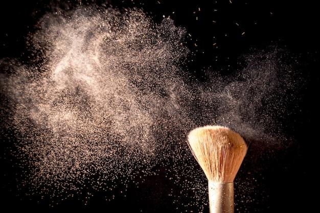 Maquillage des pinceaux avec des éclaboussures de poudre isolés sur fond noir