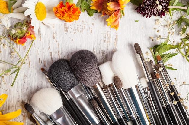Maquillage des pinceaux sur fond en bois à côté de fleurs sauvages. cosmétique professionnelle